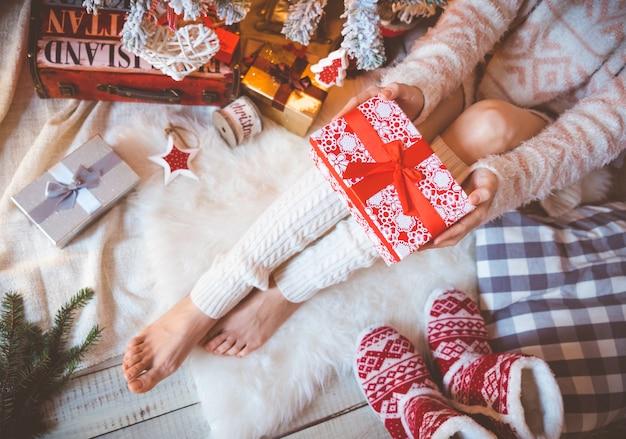 Mulher jovem e bonita em roupas quentes e aconchegantes está sentada no chão de madeira clara em sua casa brilhante perto da árvore de natal e tem uma caixa de presente nas mãos dela.