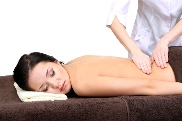 Mulher jovem e bonita em salão de spa recebendo massagem, isolado no branco