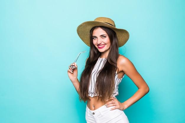 Mulher jovem e bonita em shorts jeans e camisa laranja, posando com os braços levantados. no fundo verde-azulado.