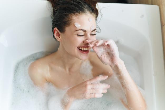 Mulher jovem e bonita em sua bela banheira branca como a neve descansa e relaxa, bela evidência, banheira com espuma