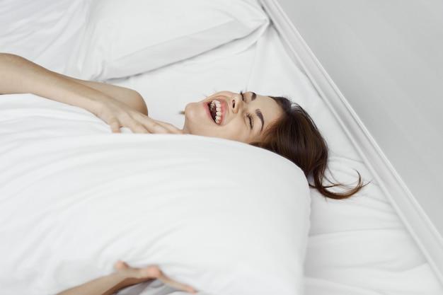 Mulher jovem e bonita em sua linda cama branca como a neve relaxa e relaxa, bela evidência