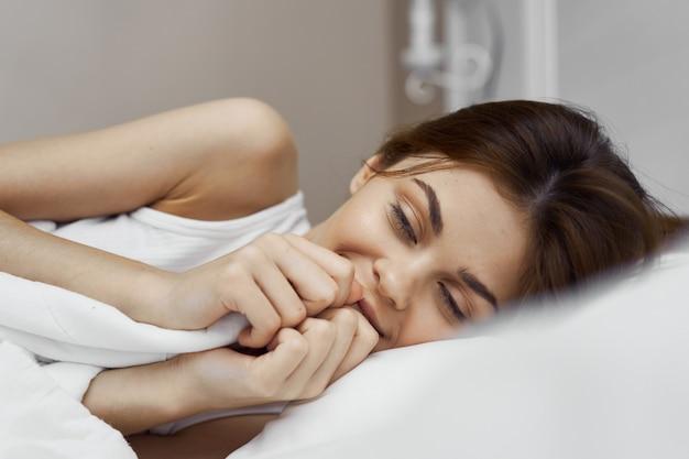 Mulher jovem e bonita em sua linda cama branca como a neve relaxa e relaxa,