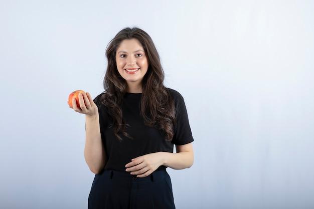 Mulher jovem e bonita em top preto posando com maçã fresca.