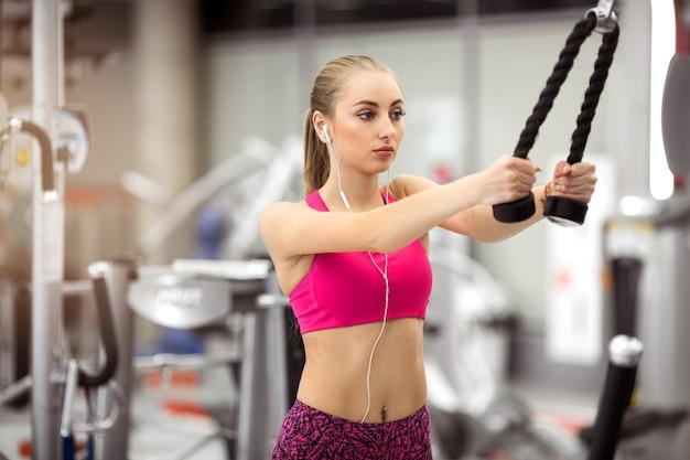 Mulher jovem e bonita em tops rosa engajada em um simulador de energia