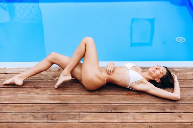 Mulher jovem e bonita em traje de banho biquíni, deitada na borda da piscina.