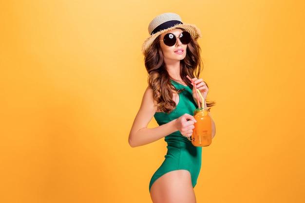 Mulher jovem e bonita em trajes de banho esmeralda e chapéu de palha segurando o jarro com bebida gelada