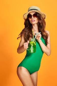Mulher jovem e bonita em trajes de banho esmeralda e chapéu de palha segurando uma jarra com bebida gelada em pé na parede amarela