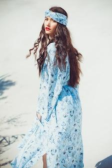 Mulher jovem e bonita em trajes de praia caminhando na areia