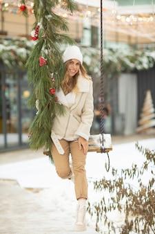 Mulher jovem e bonita em um balanço na caminhada de inverno nevado. diversão ao ar livre para as férias de inverno.