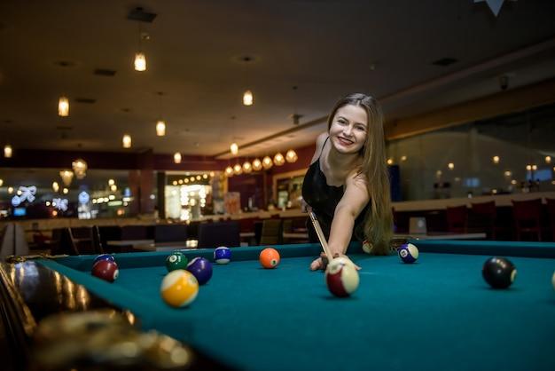 Mulher jovem e bonita em um bar jogando bilhar