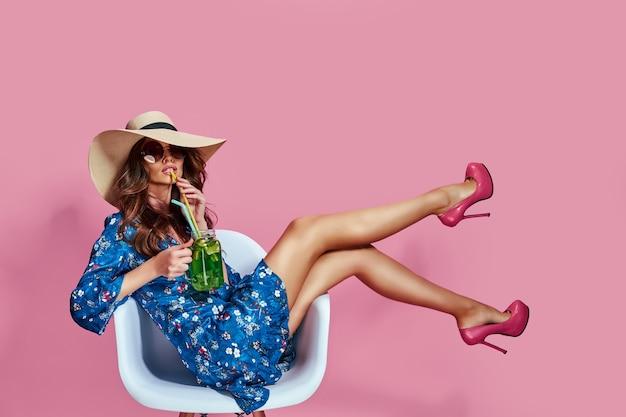 Mulher jovem e bonita em um belo vestido de primavera com estampa de flor azul e chapéu de palha em um estúdio de moda primavera verão fotos emoções fundo rosa