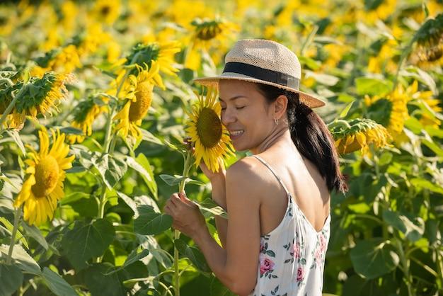 Mulher jovem e bonita em um campo de girassóis em um vestido branco. viajar no conceito de fim de semana. retrato de mulher autêntica com chapéu de palha. ao ar livre no campo de girassol.