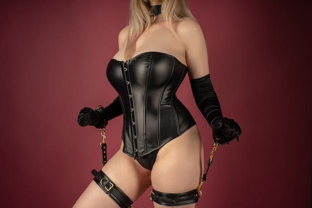 Mulher jovem e bonita em um espartilho de couro e conjunto de escravidão posando