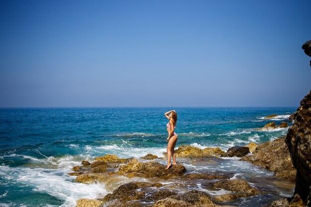 Mulher jovem e bonita em um maiô em uma praia rochosa em um dia ensolarado, contra o pano de fundo das ondas. férias na temporada de verão. foco seletivo