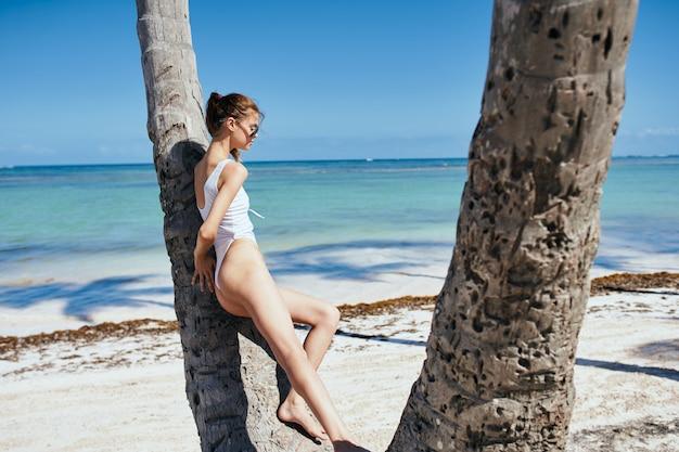 Mulher jovem e bonita em um maiô na praia perto de palmeiras