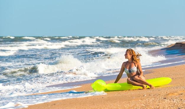 Mulher jovem e bonita em um maiô sentada em um colchão de ar na praia