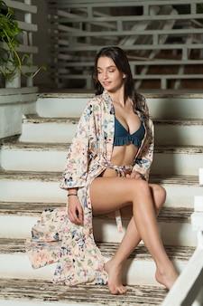 Mulher jovem e bonita em um pareo de praia em uma escada