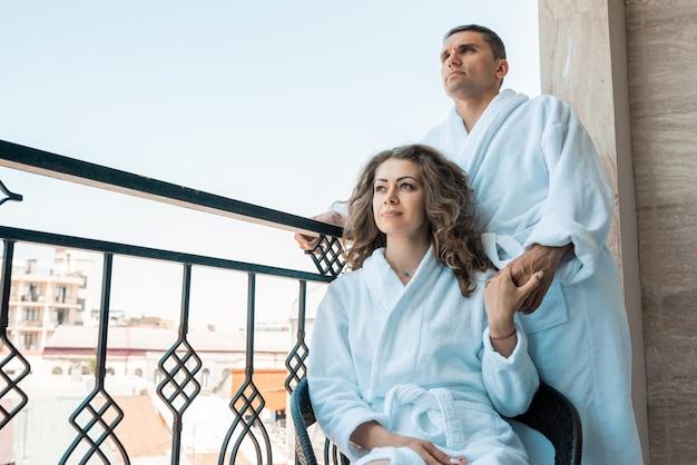 Mulher jovem e bonita em um roupão branco relaxa na varanda com seu homem.