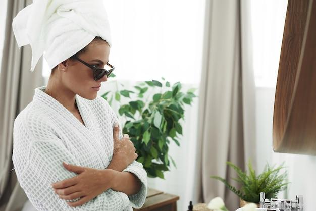 Mulher jovem e bonita em um roupão de banho, com uma toalha branca na cabeça e óculos de sol pretos, brincando na frente do espelho do banheiro.