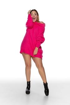 Mulher jovem e bonita em um suéter confortável rosa brilhante de manga longa isolada no estúdio branco
