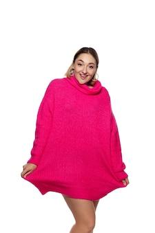 Mulher jovem e bonita em um suéter confortável rosa brilhante, manga comprida isolada no estúdio branco