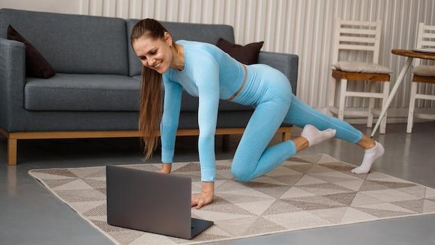 Mulher jovem e bonita em um terno azul, fazendo exercícios de fitness em casa. ela olha para seu laptop e repete os movimentos para o curso online.