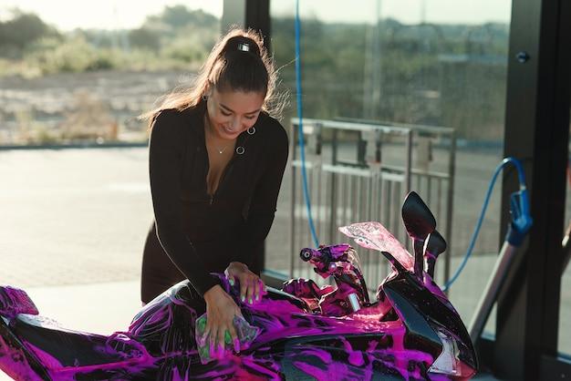 Mulher jovem e bonita em um terno preto apertado lava a motocicleta esporte e a limpa de espuma magenta.