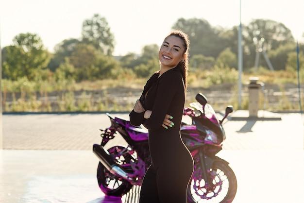 Mulher jovem e bonita em um terno preto apertado poses perto de motocicleta esporte em carro self-service