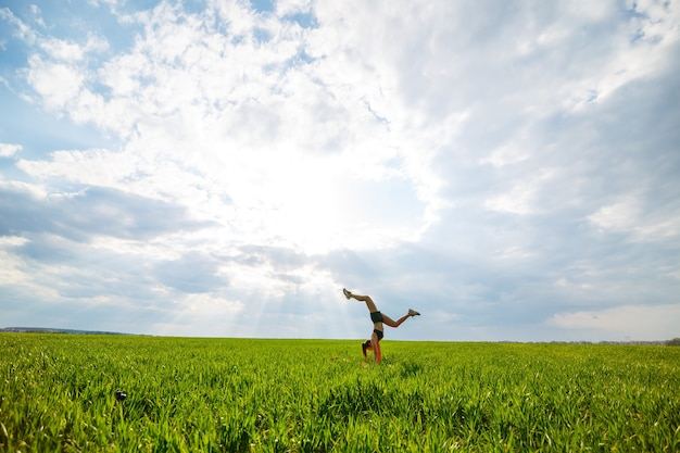 Mulher jovem e bonita em um top preto e shorts executa uma parada de mão. uma modelo está de pé, fazendo exercícios de ginástica contra o céu azul. conceito de estilo de vida saudável