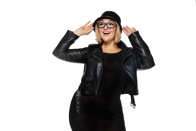 Mulher jovem e bonita em um traje preto elegante isolado no fundo branco do estúdio.
