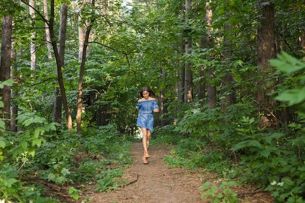 Mulher jovem e bonita em um vestido correndo na floresta de verão