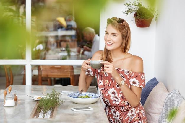 Mulher jovem e bonita em um vestido de café
