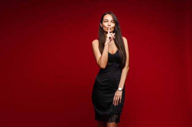 Mulher jovem e bonita em um vestido de noite preto com o dedo indicador na boca, fazendo sinal de silêncio, pedindo para guardar segredo