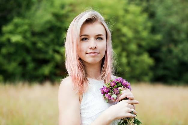 Mulher jovem e bonita em um vestido de renda vintage branco com cabelo rosa e um chapéu atravessa o prado