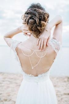 Mulher jovem e bonita em um vestido elegante. vista traseira da moda do casamento.