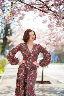 Mulher jovem e bonita em um vestido em árvores florescendo de sakura. é um dia quente e ensolarado de primavera lá fora