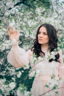 Mulher jovem e bonita em um vestido leve na superfície de um jardim florido