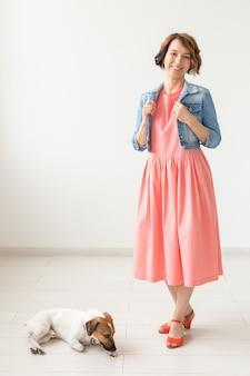 Mulher jovem e bonita em um vestido longo e elegante e uma camisa jeans posando em uma superfície branca com