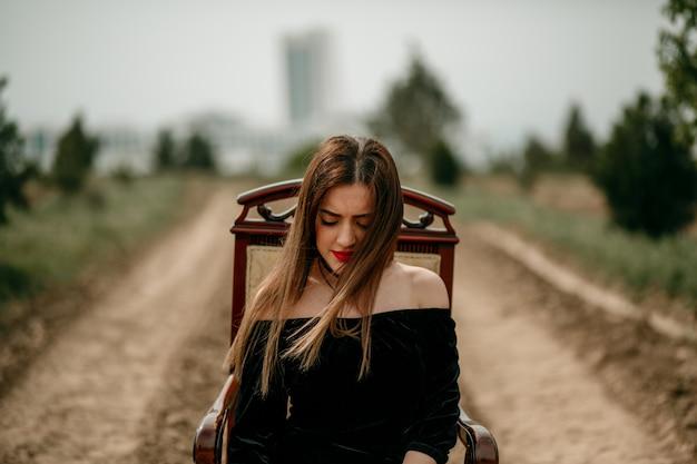 Mulher jovem e bonita em um vestido preto posa para um fotógrafo