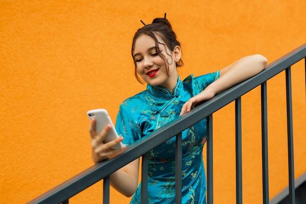 Mulher jovem e bonita em um vestido tradicional com telefone celular
