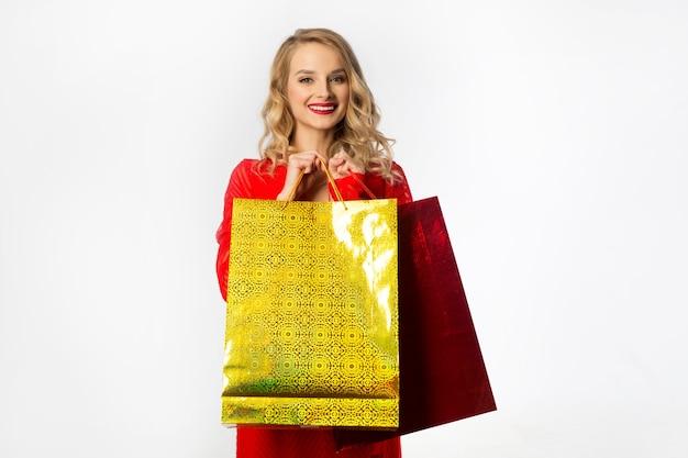 Mulher jovem e bonita em um vestido vermelho com pacotes nas mãos em um fundo branco