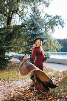 Mulher jovem e bonita em um vestido vermelho e um chapéu elegante no parque outono, grávida feliz, garota em uma manta.