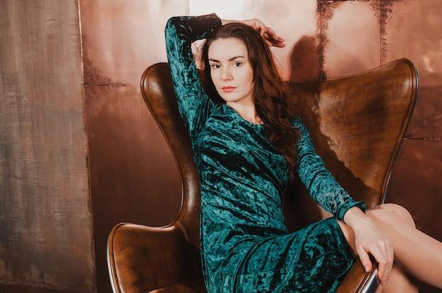 Mulher jovem e bonita em uma cadeira de couro marrom