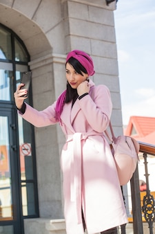 Mulher jovem e bonita em uma caminhada falando ao telefone
