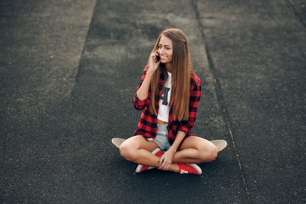 Mulher jovem e bonita em uma camisa branca, camisa vermelha, shorts e tênis, sentado em um skate e falando no telefone celular
