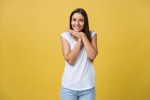 Mulher jovem e bonita em uma camisa branca está segurando a cabeça nas mãos, sorrindo e olhando para a câmera.