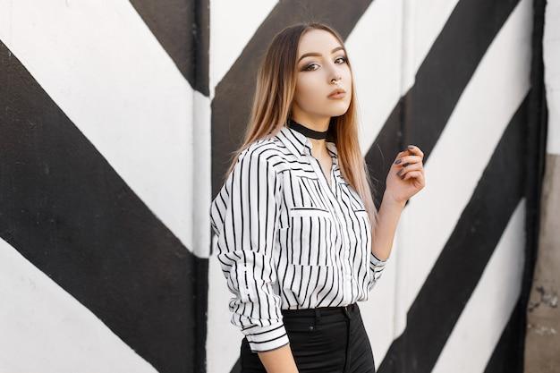 Mulher jovem e bonita em uma camisa preta e branca da moda em uma linha com um piercing no nariz em jeans pretos em um colar de veludo posando perto de uma parede vintage listrada