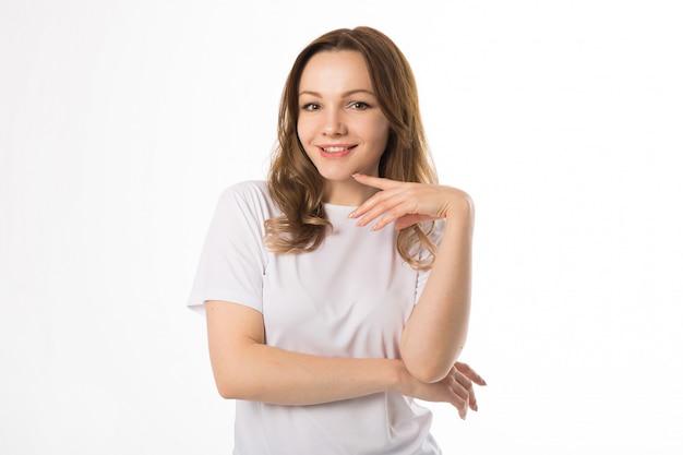Mulher jovem e bonita em uma camiseta branca sobre fundo branco