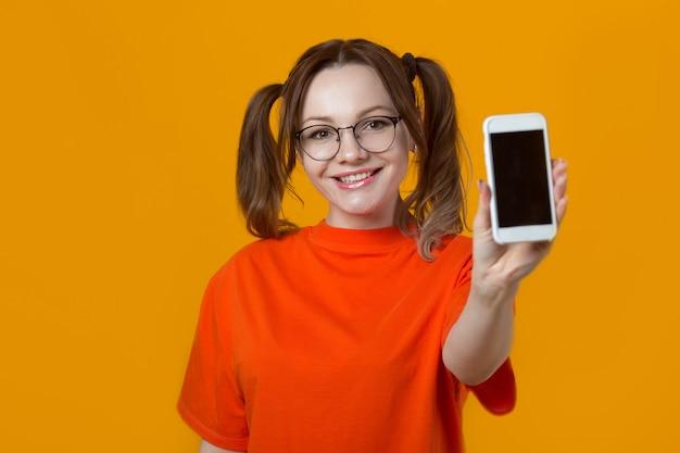 Mulher jovem e bonita em uma camiseta com um telefone na mão