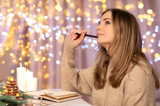 Mulher jovem e bonita em uma camisola de malha bege escrevendo uma carta, planos de metas ou uma lista de desejos para o natal no interior festivo em casa